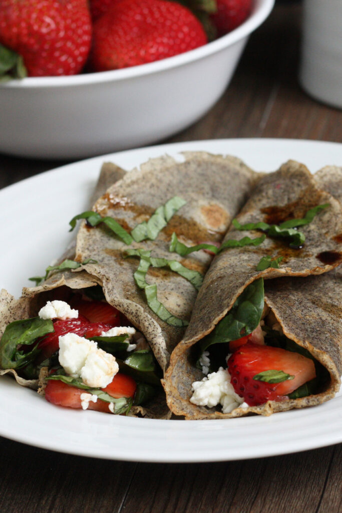 Two buckwheat crepes filled with strawberry spinach filling. Close up.