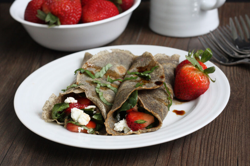 Two buckwheat crepes with strawberry spinach filling on white plate.