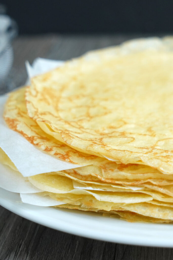 Stack of finished cooked crepes with parchment between each crepe.