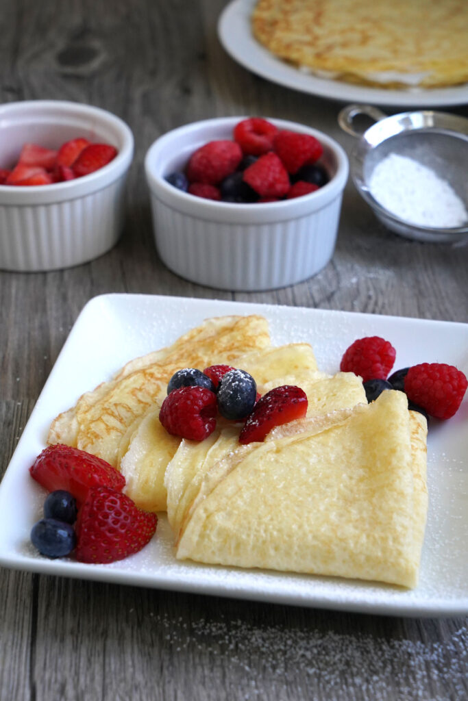 Crepes folded into a triangle, sprinkled with powdered sugar and served with fresh fruit.