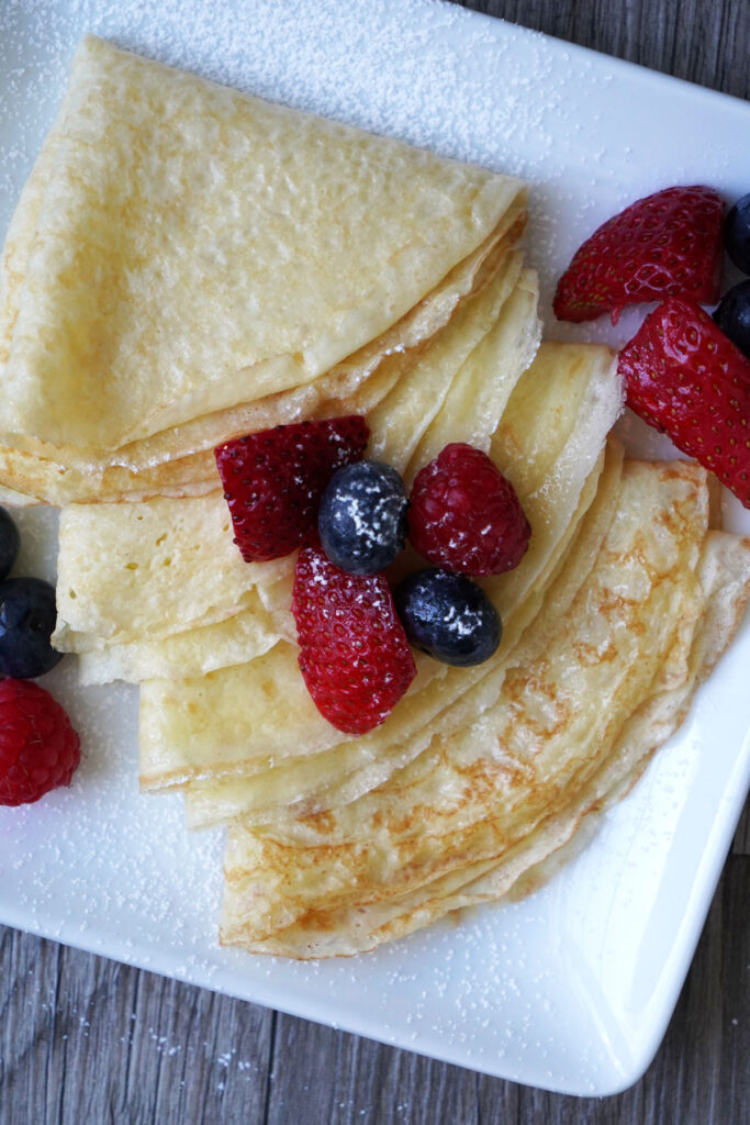 Close up of crepes, folded into triangles, served with fresh fruit.