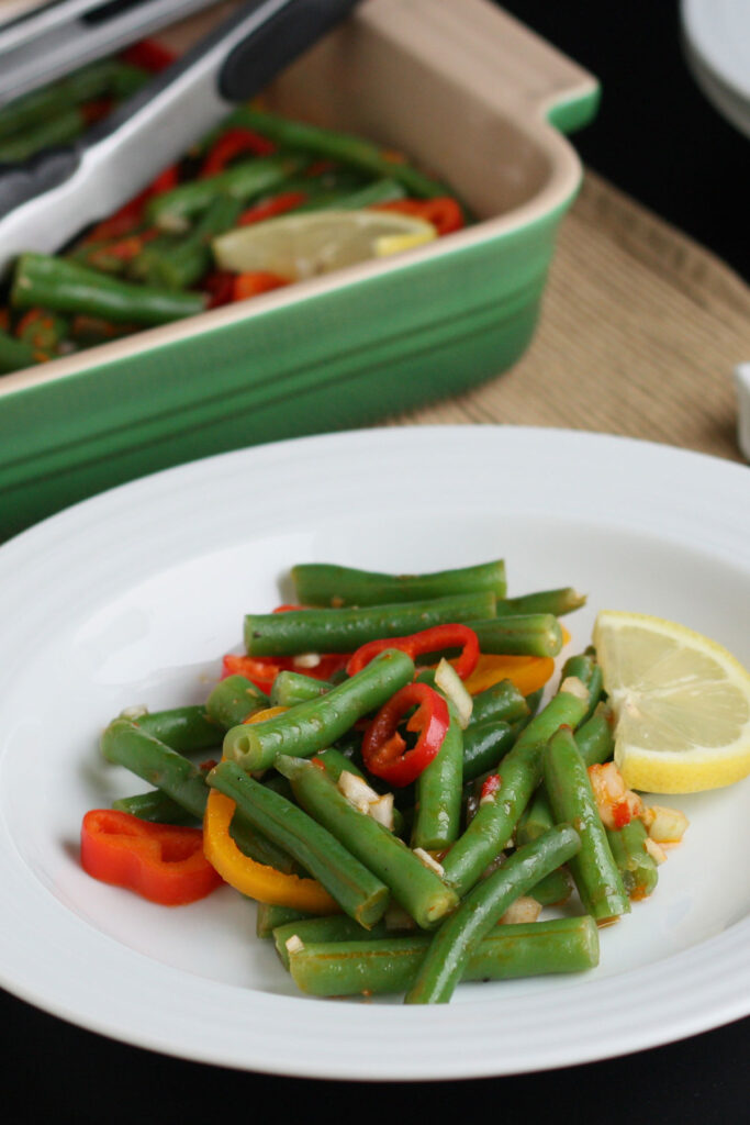 Serving of green bean salad with lemon harissa dressing on a white plate.