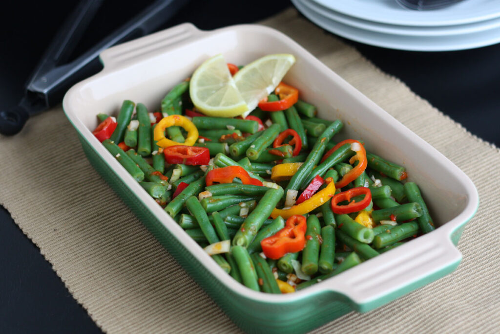 Green Bean Salad with plates on the side.