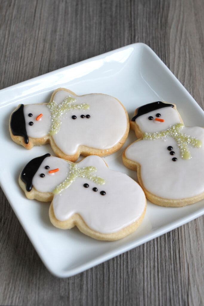 Three snowman cookies on a white square plate.