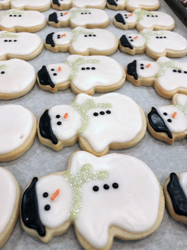 Finished snowman cookies drying in a sheet pan.