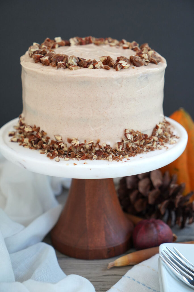 Sweet potato cake decorated with candied pecans on wooden and marble cake stand with acorns and squash in background.
