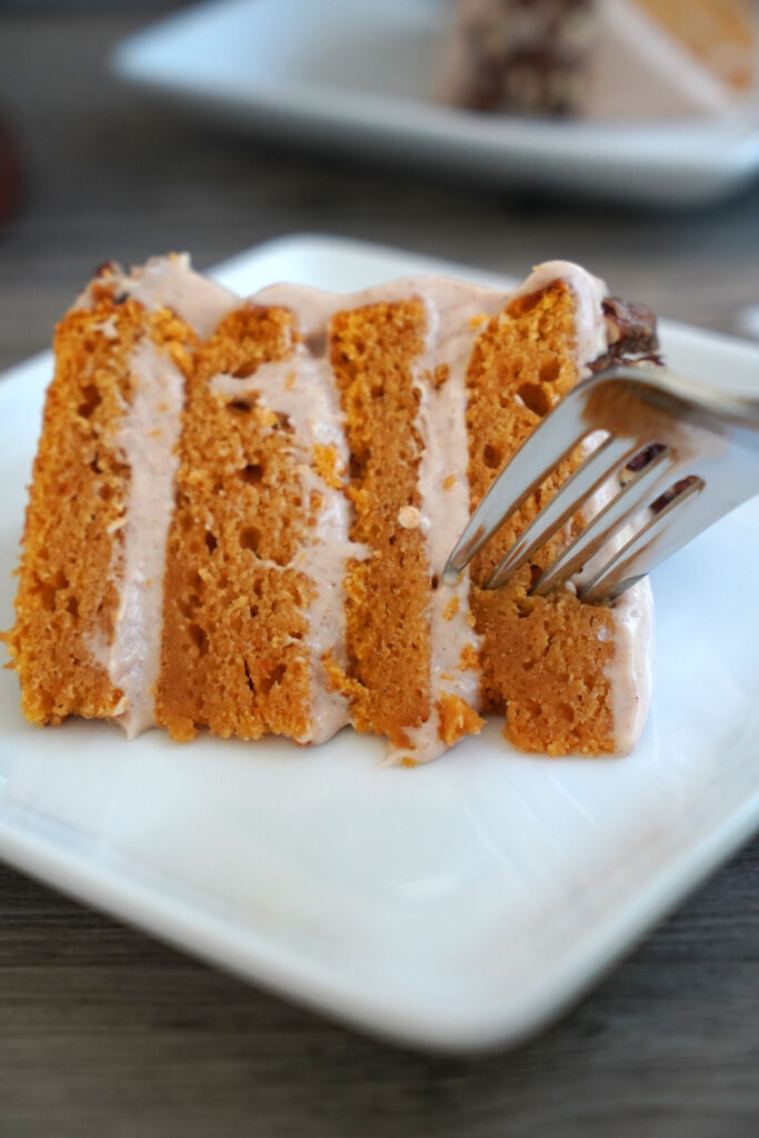 Fork being inserted into a slice of cake.
