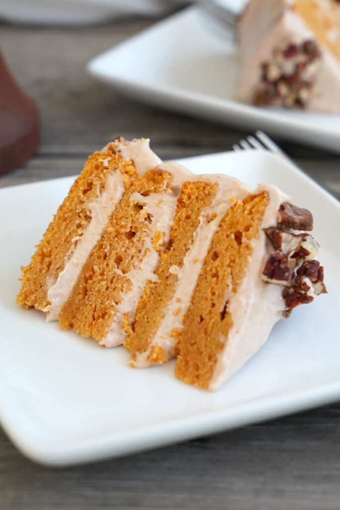 Close up view of a slice of sweet potato cake with cinnamon frosting and candied pecans.
