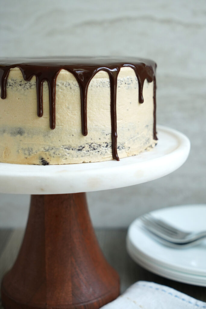 Mexican Chocolate cake with espresso  buttercream on a marble cake stand with a wooden base.