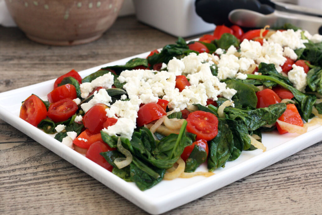 White platter with spinach salad.