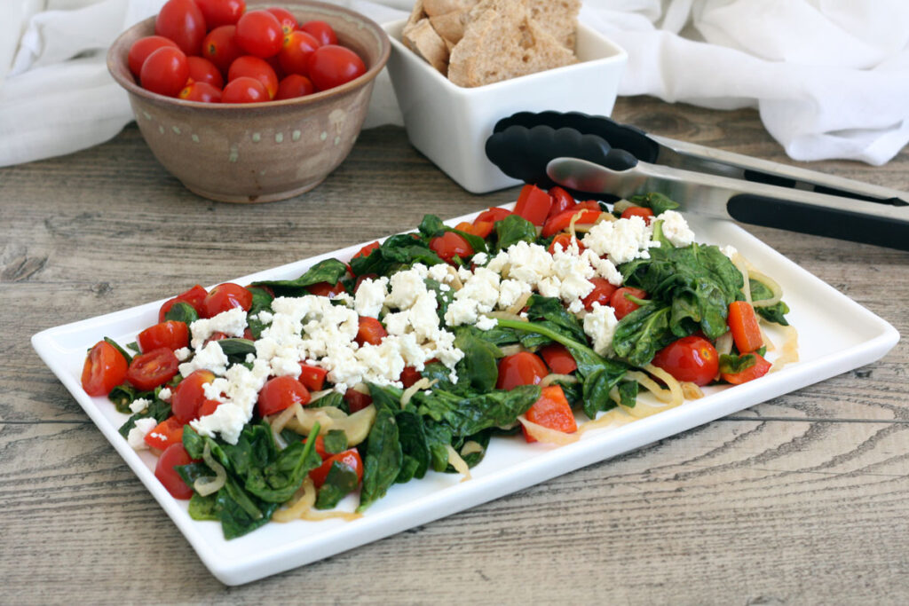 Platter of spinach salad with bread and more cherry tomatoes in the back ground.