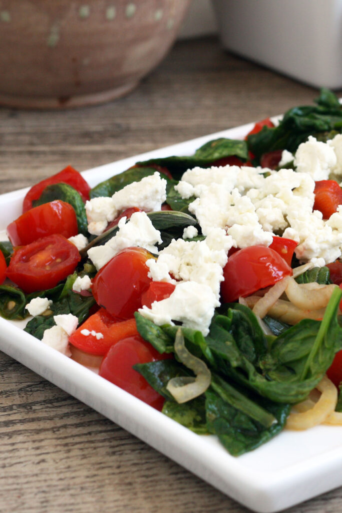 Close up view of warm spinach salad.