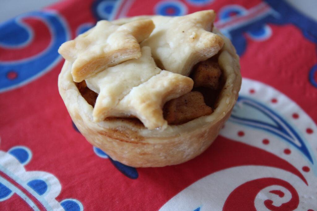 One mini apple pie on a napkin.