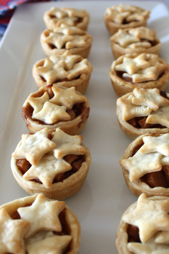 Mini apple pies with star decorations on a white platter.
