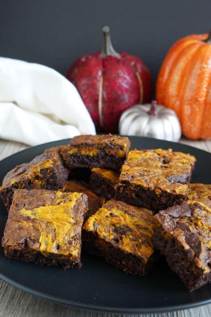 Pumpkin brownies on a black plate with decorative pumpkins in background.