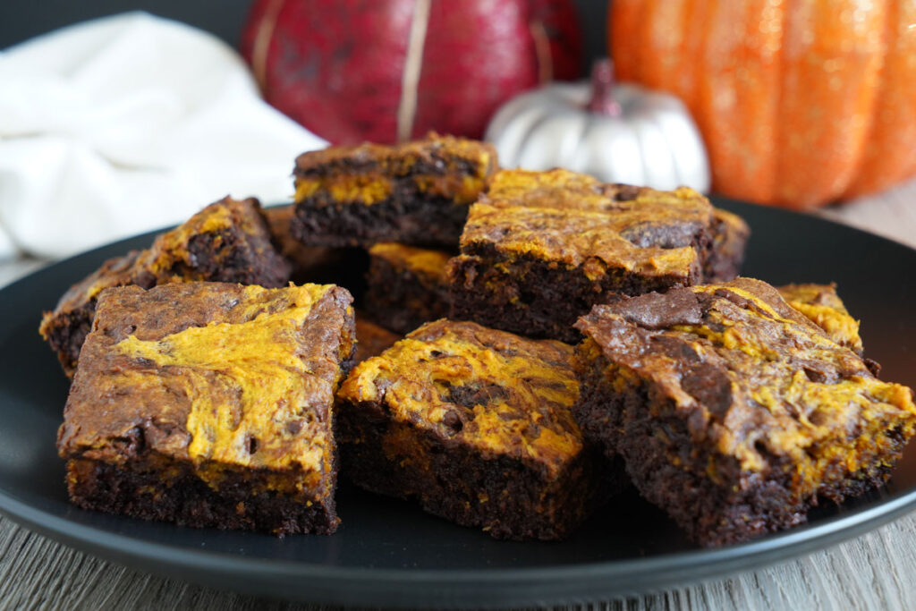 Pumpkin brookies on a black platter with pumpkins in the background.