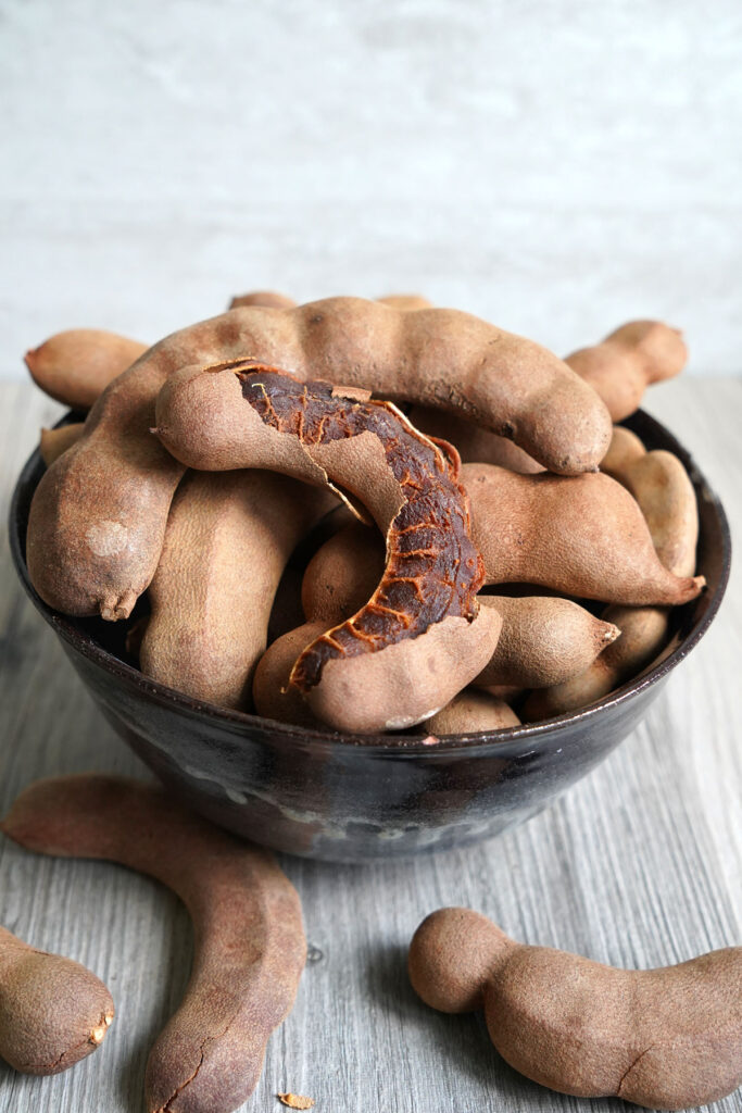 Tamarind pods in a bowl with one pod having the shell peeled open.