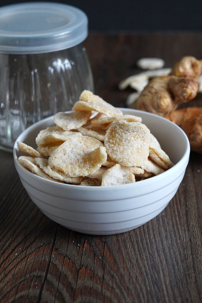 Crystallized candied ginger slices in a white bowl.