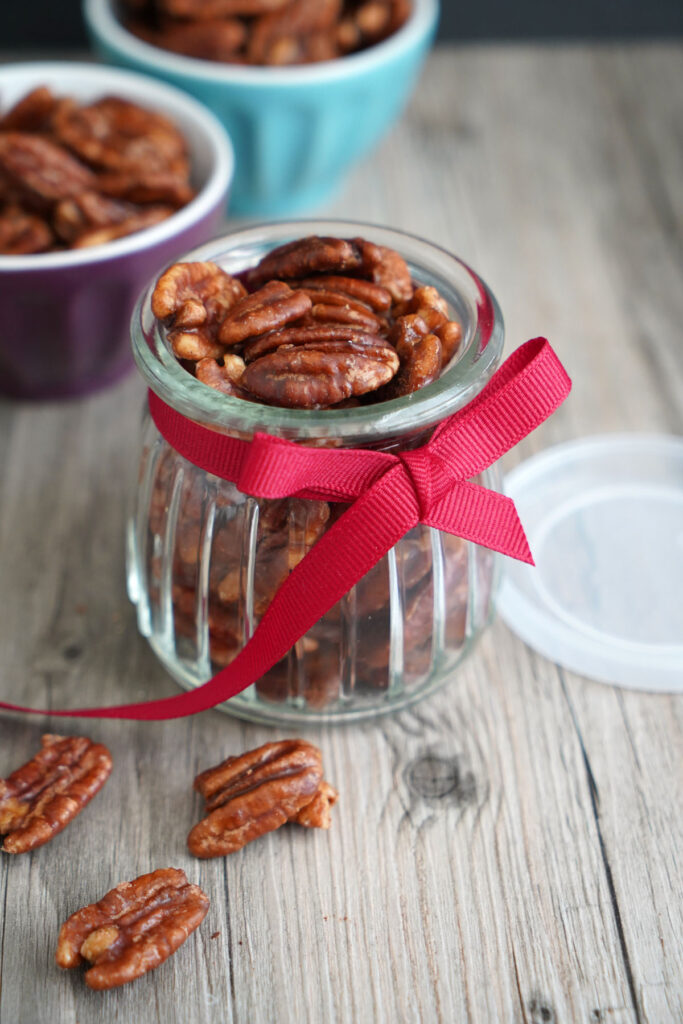 Candied pecans in small jar with red ribbon.