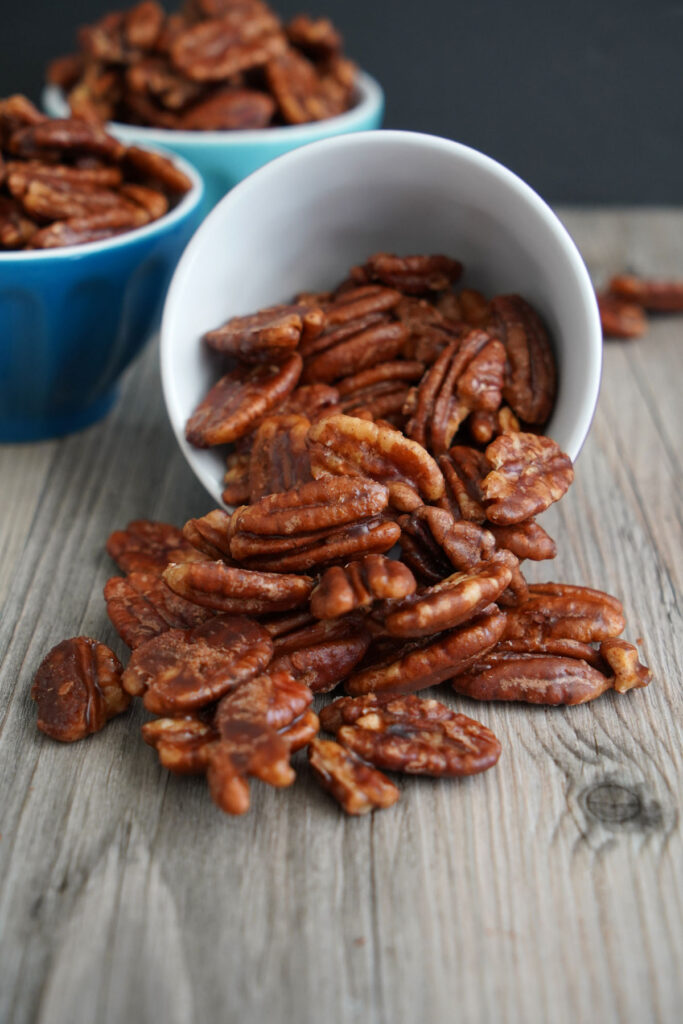 Candied pecans spilled out of a small bowl.