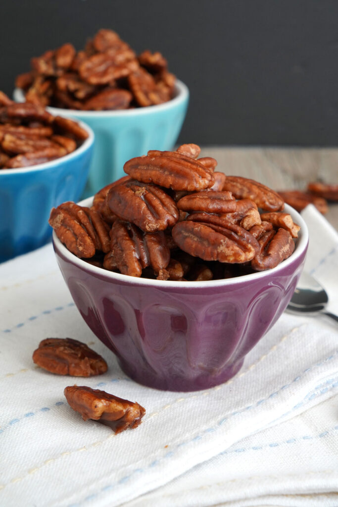 Candied pecans in small purple bowl on top of napkin.