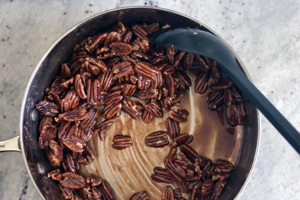 Pecans being coated with sugar spice mix.