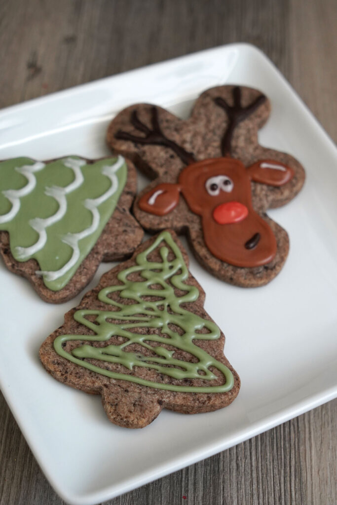 Decorated tree and reindeer cookies on a white plate.