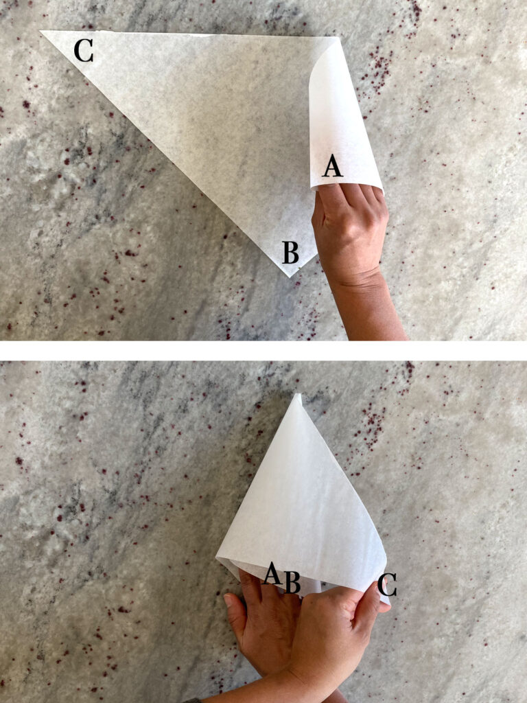 Parchment paper triangle being rolled into cone shape.