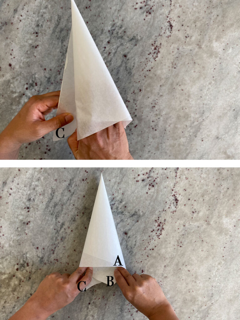 Final steps of parchment triangle being rolled into cone shape.