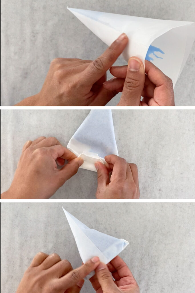 Paper cone being folded after filling with icing.