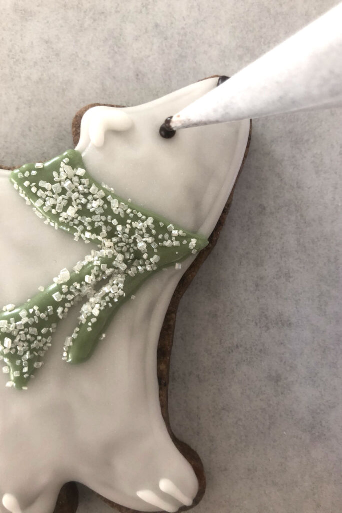 Polar Bear shaped cookie being decorated using a parchment cone.