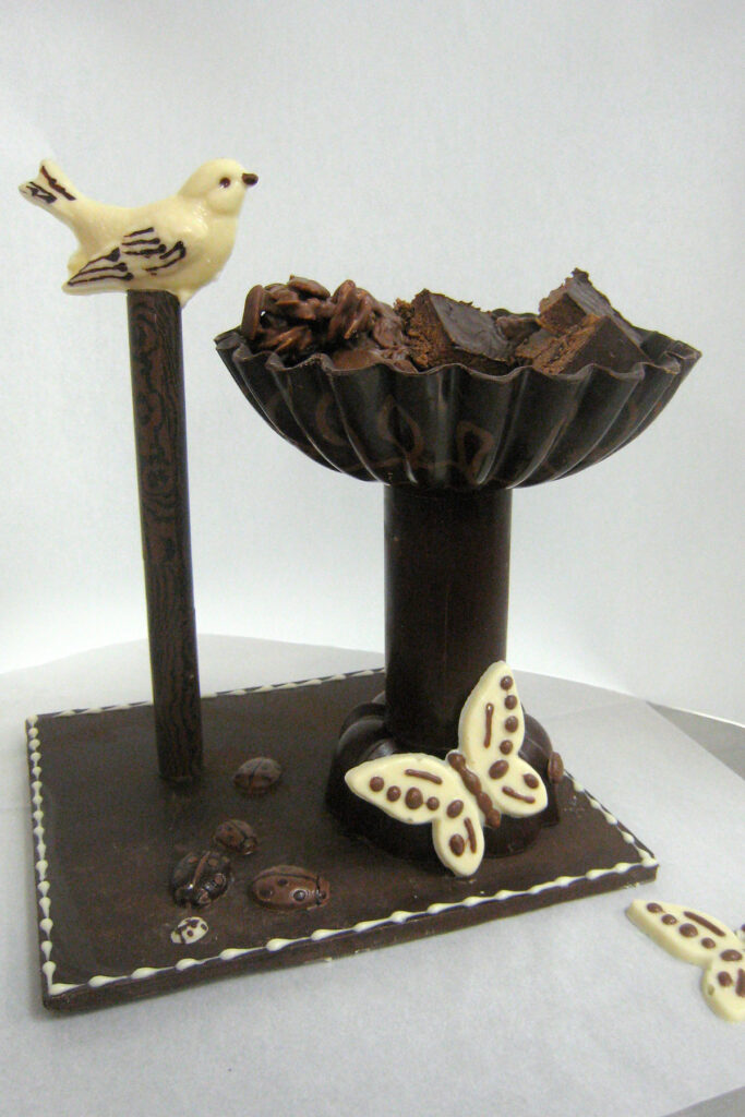 Chocolate sculpture of bird and bird bath made with tempered chocolate.