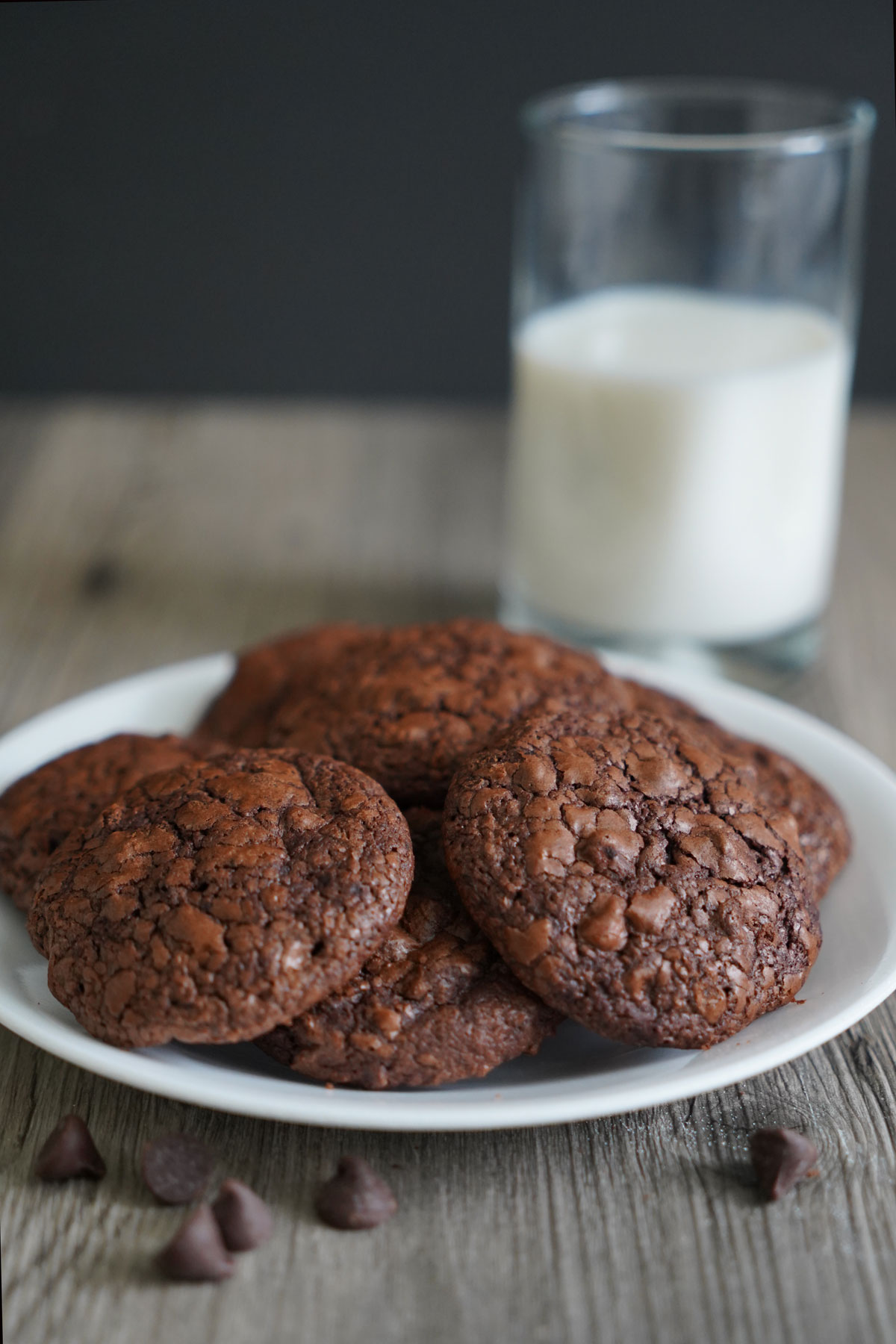 Brownie cookies on a white plate with glass of milk.