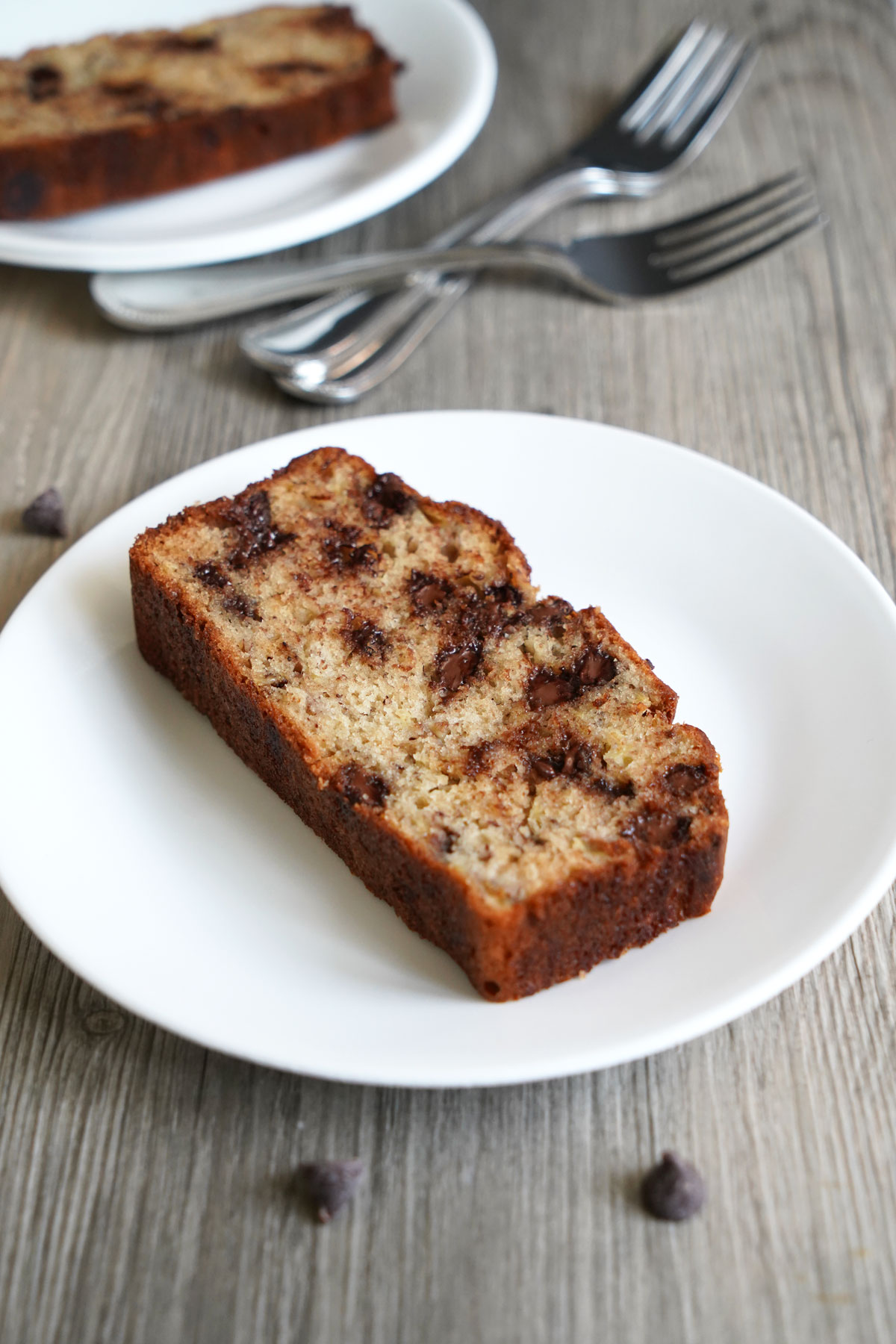 Slices of chocolate chip banana bread on plates next to forks.